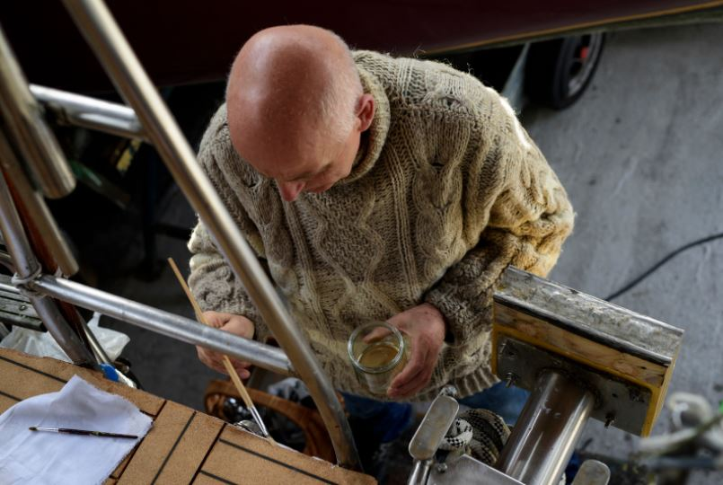 a bald guy painting on his boat